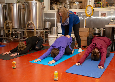Yoga instructor Laura Schultz teaches area residents stretching exercises during Yoga & Beer with Akasha held Wednesday, December 26, 2018 at the Crystal Lake Brewery in Crystal Lake. KKoontz – For Shaw Media