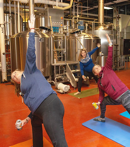 Beth Alberger (Left) and Geri Schneff (Right) learn stretches from instructor Laura Shultz during Yoga & Beer with Akasha held Wednesday, December 26, 2018 at the Crystal Lake Brewery in Crystal Lake. KKoontz – For Shaw Media