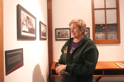 """Candace H. Johnson-For Shaw Media Polly Machak, of Grayslake looks at a photo of a group of students at the Elementary School in Waukegan, Circa 1900, after listening to the discussion of the book, """"200 Objects That Made History in Lake and McHenry Counties,"""" during the Illinois Bicentennial Celebration at the Bess Bower Dunn Museum in Libertyville. Free programs are offered at the Dunn Museum every 1st and 3rd Thursday evening. (12/20/18)"""