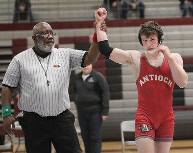 Candace H. Johnson-For Shaw Media Referee Tony Clark, of Zion holds up Antioch's Niall Schoenfelder's, 17, arm as he celebrates his win with a pin against McHenry's Aidan Ferguson, 16, in the 195 lb. weight class during the Holiday Duals wrestling quad at Antioch Community High School. (12/22/18)