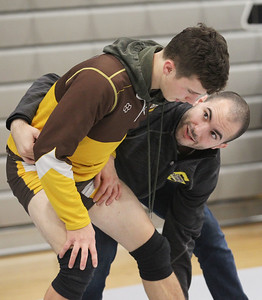Candace H. Johnson-For Shaw Media Carmel's Vincent Swindell, 17, gets some help from his brother, Frankie, an assistant varsity coach, both of Grayslake, practicing finishing takedowns as he competes in the 145 lb. weight class during the Holiday Duals wrestling quad at Antioch Community High School. (12/22/18)