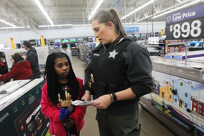 Candace H. Johnson-For Shaw Media Neveah C, 10, of Round Lake Beach talks to Dana Dingman, deputy coroner, with the Lake County Coronor's Office, about the list of things she wants to get during the Lake County Sheriff's Office Shop with a Sheriff at the Walmart in Round Lake Beach. (12/18/18)