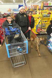 Candace H. Johnson-For Shaw Media Edwin Hernandez, 10, of Round Lake and his mother, Maria, go shopping with Jason Patt, chief of the Lake County Coroner's office, (center) and his K-9 tracker, Bones, during the Lake County Sheriff's Office Shop with a Sheriff at Walmart in Round Lake Beach. (12/18/18)