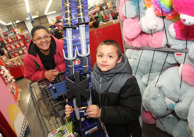 Candace H. Johnson-For Shaw Media Kirsten Fletcher, of Round Lake stands close to her son, Artistic, 6, as he shows off the toy he picked out as they wait on line to check out during the Lake County Sheriff's Office Shop with a Sheriff at Walmart in Round Lake Beach. (12/18/18)