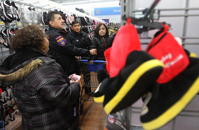 Candace H. Johnson-For Shaw Media Leopold Seme, court security officer, and Ricky Ignacio, auxiliary deputy, (both center) shop with Rosalia Flores, of Round Lake Beach and her daughter, Angela, 5, in the shoe department during the Lake County Sheriff's Office Shop with a Sheriff at Walmart in Round Lake Beach. (12/18/18)