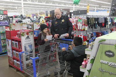 Candace H. Johnson-For Shaw Media John Doherty, a deputy chief with the auxiliary, (center) goes over a shopping list with Natalie, P., 10, of Round Lake Beach and her brother, Jayden, 5, during the Lake County Sheriff's Office Shop with a Sheriff at Walmart in Round Lake Beach. (12/18/18)