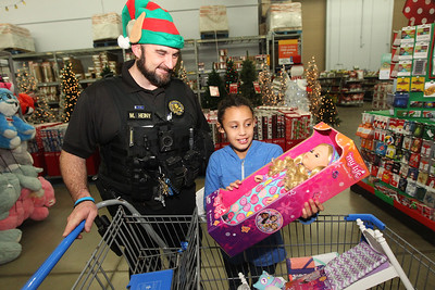 Candace H. Johnson-For Shaw Media Mark Heiny, deputy sheriff, talks with Jaelynn Hyc, 8, of Round Lake Beach about the doll she picked out as they wait on line to check out during the Lake County Sheriff's Office Shop with a Sheriff at Walmart in Round Lake Beach. (12/18/18)