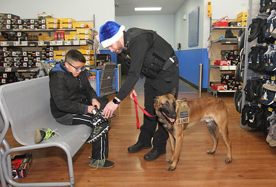 Candace H. Johnson-For Shaw Media Edwin Hernandez, 10, of Round Lake gets some help trying on shoes from Jason Patt, chief coroner with the Lake County Coroner's office, during the Lake County Sheriff's Office Shop with a Sheriff at Walmart in Round Lake Beach. (12/18/18)