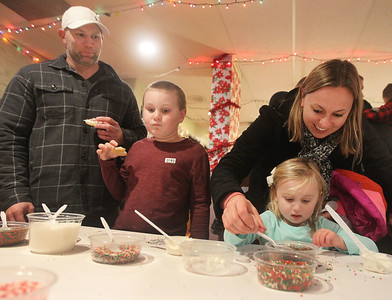 Candace H. Johnson-For Shaw Media Jason and Carri McGahan, of Grayslake help their children, Chase, 7, and Callie, 3, decorate cookies at The Oasis during the Grayslake Tree Lighting Festivities in downtown Grayslake. The cookies were provided by Somethings Brewing from Grayslake.(11/29/19)