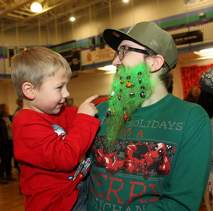 Candace H. Johnson-For Shaw Media Benjamin Burak, 4, of Lindenhurst points to the ornaments on his father, Robert's, beard during the Holiday Tree Lighting at the Lippert Community Center in Lindenhurst. (12/7/19)