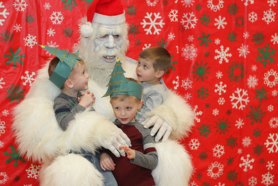 Candace H. Johnson-For Shaw Media Dylan Knutson, 5, of Lake Villa and his brothers, Evan, 5, and Tyler, 4, visit with the Yeti (an Abominable Snowman) and get their photo taken with him during the Holiday Tree Lighting at the Lippert Community Center in Lindenhurst. (12/7/19)