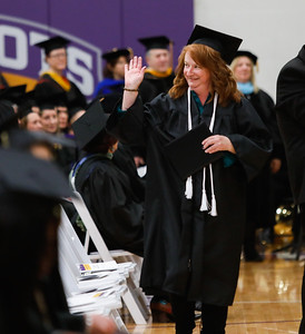Jodi Clark gives a wave after receiving her diploma in business management at the McHenry County College winter commencement on Saturday in Crystal Lake. Photo by Bev Horne