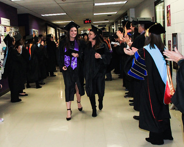Dana Ehardt, left, and Dawn Lyons, right, walk down the hall to applause from faculty after getting their diplomas at McHenry County College graduation on Saturday in Crystal Lake. Photo by Bev Horne