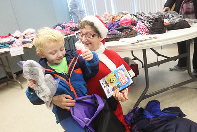 Candace H. Johnson-For Shaw Media Phillip D., 4, of Ingleside shows Nuala Watson, of Twin Lakes, Wis., a volunteer, the items he picked out to take home, including a DVD, during the Antioch Traveling Closet Winter Giveaway event at the Antioch Senior Center in Antioch.  (12/14/19)