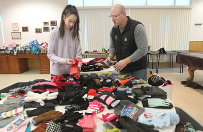 Candace H. Johnson-For Shaw Media Larkin Murphy, 14, of Antioch and her father, Chris, put donated gloves and hats on a table the day before for the Antioch Traveling Closet Winter Giveaway event at the Antioch Senior Center in Antioch.  (12/14/19)
