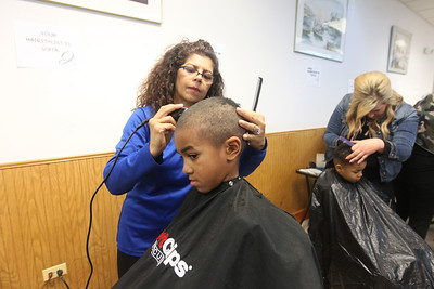 Candace H. Johnson-For Shaw Media Hair stylists Sofia Gilmore and Lauren Sunde, both of Antioch give haircuts to Elijah Duckworth, 6, of Zion and his brother, Zechariah, 4, during the Antioch Traveling Closet Winter Giveaway event at the Antioch Senior Center in Antioch.  (12/14/19)