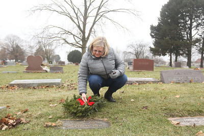 Candace H. Johnson-For Shaw Media Christine Merevick, of Round Lake straightens the bow on the wreath laid at the grave of Jesse Patterson, a U.S. Navy veteran who served in both Korea and Vietnam, during Wreaths Across America at the Warren Funeral Home Cemetary in Gurnee.  (12/14/19)
