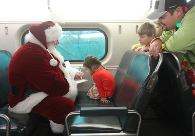 "Candace H. Johnson-For Shaw Media Santa signs the book called, ""The Polar Express,"" for Anastasia Morales, 3, of Antioch after she won the book in a raffle as they travel back by train to Antioch from the North Pole during the North Pole Express. Anastasia's brothers, Julian, 12, Jackson, 9, and their father, Eric, watched them. (12/16/19)"