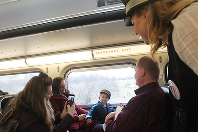 Candace H. Johnson-For Shaw Media Nicole Girardi, of Antioch takes a photo of her son, Oliver, 2, as he wears a Conductor's hat sitting next to her sister, Ashley Lewis, of Lake Villa and father, Don White, of Antioch as they ride the North Pole Express from Antioch. Sandra Simon, of Antioch, portrays a conductor, as she stands next to them. The Village of Antioch Parks & Recreation sponsored the event. (12/16/19)