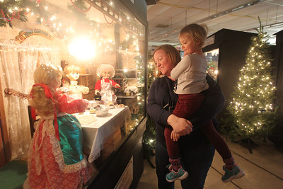 "Candace H. Johnson-For Shaw Media Megan Cline, of Lake Villa holds her daughter, Lila, 5, as they look at a supersized shadowbox titled, ""Four Generations Keeping the Tradition,"" in the indoor showroom of Kringle's Christmas Village at #510 Orchard Street in downtown Antioch. The Village is open daily from 10:00am until 8:00 pm through January 1st, 2020. (12/21/19)"