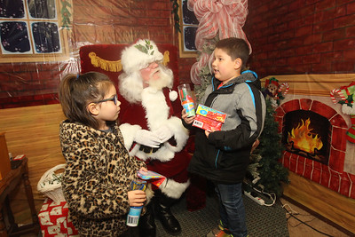 Candace H. Johnson-For Shaw Media Phoebe Shortess, 5, of Lindenhurst and her brother, Xavier, 6, tell Santa what they want for Christmas at Santa's Frozen Village at 882 Main Street in downtown Antioch. Santa's Village was sponsored by the Antioch Chamber of Commerce. (12/21/19)