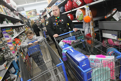 Candace H. Johnson-For Shaw Media Carmine Levas, 8, of Antioch pushes a cart alongside Greg Regnier, a Lake Villa police officer, as they go shopping during Lake Villa's Shop with a Cop at Walmart in Round Lake Beach. (12/19/19)