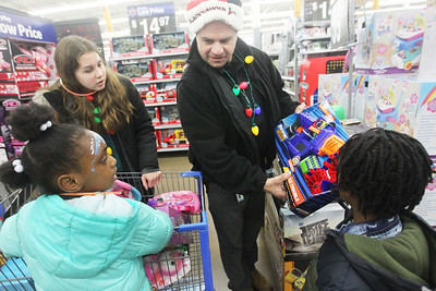 Candace H. Johnson-For Shaw Media Josie Caliendo, 13, helps her father, Anthony, a Lake Villa police officer, work with Dashanti Sims, 6, of Lindenhurst and her brother, Dasean, 8, picking out toys during Lake Villa's Shop with a Cop at Walmart in Round Lake Beach. (12/19/19)