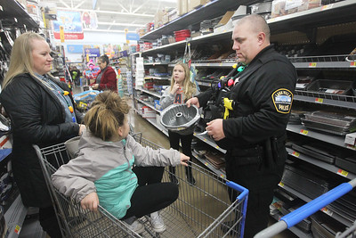 Candace H. Johnson-For Shaw Media Lake Villa Police Officer Greg Regnier (on right) and his wife, Corinne, help Burke Shea, 9, pick out a baking pan for her mother as Mariella Levas, 6, both of Antioch sits in the shopping cart during Lake Villa's Shop with a Cop at Walmart in Round Lake Beach. (12/19/19)