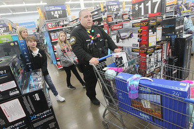 Candace H. Johnson-For Shaw Media Lake Villa Police Officer Greg Regnier walks with Stephanie Levas, her son, Cross, 10, and Burke Shea, 9, all of Antioch as they go shopping during Lake Villa's Shop with a Cop at Walmart in Round Lake Beach. (12/19/19)