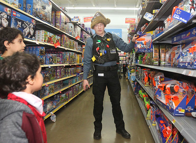 Candace H. Johnson-For Shaw Media Tyler Schaefer, Community Service Officer with the Lake Villa Police Dept., helps Yaya Kadhim, 10, of Lake Villa and his brother, Eissa, 5, pick out toys during Lake Villa's Shop with a Cop at Walmart in Round Lake Beach. (12/19/19)