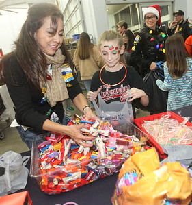 Candace H. Johnson-For Shaw Media Patty Ibarra, of Round Lake Beach, the OTC department manager, gives candy to Makayla Jones, 12, of Lake Villa after she went shopping with Rochelle Tisinai, a Lake Villa police officer (on right) during Lake Villa's Shop with a Cop at Walmart in Round Lake Beach. (12/19/19)