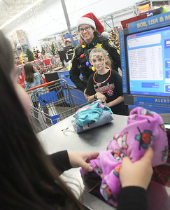 Candace H. Johnson-For Shaw Media Jessica Lara, 16, of Round Lake, associate cashier, rings up Rochelle Tisinai, Lake Villa police officer, after she helped Makayla Jones, 12, of Lake Villa pick out clothes during Lake Villa's Shop with a Cop at Walmart in Round Lake Beach. (12/19/19)
