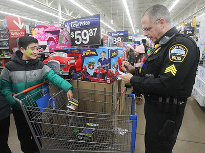 Candace H. Johnson-For Shaw Media Emiliano Hernandez, 11, of Lake Villa puts a toy in the cart as Sgt. Mark Fragale with the Lake Villa Police Dept. keeps track of his spending, up to one hundred dollars, during Lake Villa's Shop with a Cop at Walmart in Round Lake Beach. (12/19/19)