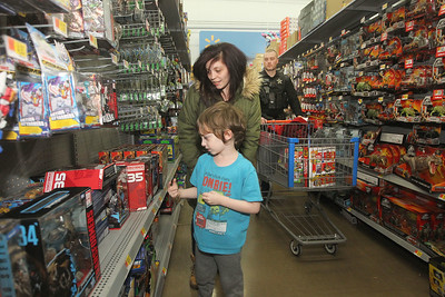 Candace H. Johnson-For Shaw Media Kayla Tinkes, of Lake Villa and her son, Logan Stewart, 7, walk down the isle with Ryan Dionne, a Lake Villa police officer, as they shop for toys for Logan, during Lake Villa's Shop with a Cop at Walmart in Round Lake Beach. (12/19/19)