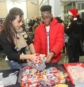 Candace H. Johnson-For Shaw Media Patty Ibarra, of Round Lake Beach, the OTC department manager, gives candy to Jediah Bukassa, 13, of Lake Villa during Lake Villa's Shop with a Cop at Walmart in Round Lake Beach. (12/19/19)