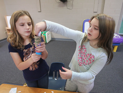 Candace H. Johnson-For Shaw Media Callie Hinze gets some help making a New Year's popper from Shannon McGrouary, both 9, of Grayslake during Winter Camp with a New Year's Party theme at the Grayslake Community Park District's Recreational Center in Grayslake. (12/30/19)