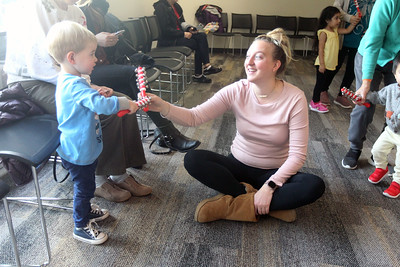 "Candace H. Johnson-For Shaw Media Blair Grigoletti, of Mundelein and her nephew, Luke, 2, play with handbells to the song, ""Jingle Bells,"" during the Winter Dance Party at the Wauconda Area Library. (12/26/19)"