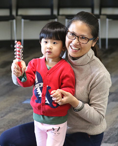 "Candace H. Johnson-For Shaw Media Sunny Lu, 3, of Wauconda and her mother, Lucy, play with handbells to the song, ""Jingle Bells,"" during the Winter Dance Party at the Wauconda Area Library. (12/26/19)"
