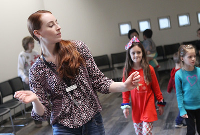 Candace H. Johnson-For Shaw Media Jenny Barreca, of Mundelein, Kid City assistant, dances with children to the music during the Winter Dance Party at the Wauconda Area Library. (12/26/19)