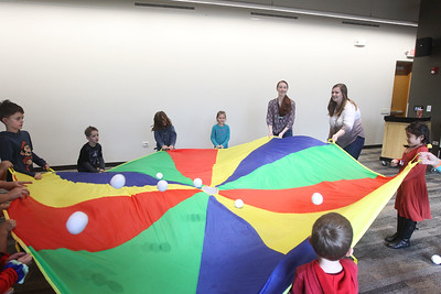Candace H. Johnson-For Shaw Media Jenny Barreca, of Mundelein and Dana Postl, of Island Lake, both Kid City assistants, use a parachute and bouncing plush snowballs to play with a group of children during the Winter Dance Party at the Wauconda Area Library. (12/26/19)