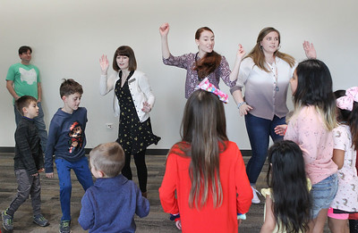 "Candace H. Johnson-For Shaw Media Stefanie Molinaro, of Crystal Lake, public services associate, Jenny Barreca, of Mundelein and Dana Postl, of Island Lake, both Kid City assistants, dance with a group of children to the song, ""Hokey Pokey,"" during the Winter Dance Party in the Lincoln Room at the Wauconda Area Library. (12/26/19)"