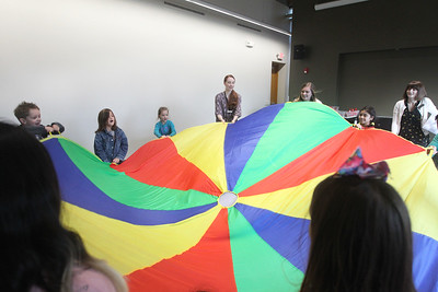 Candace H. Johnson-For Shaw Media Jenny Barreca, of Mundelein, Dana Postl, of Island Lake, both Kid City assistants, and Stefanie Molinaro, of Crystal Lake, public services associate, use a parachute to play with a group of children during the Winter Dance Party at the Wauconda Area Library. (12/26/19)
