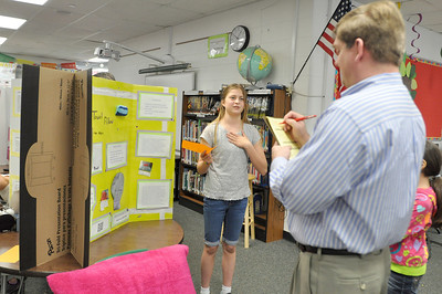 Sarah Minor — sminor@shawmedia.com Tess Klygis, 11, of Elm School presents her invention, the Towel Pillow, to fifth grade teacher Matt Haeger on Tuesday, May 7.