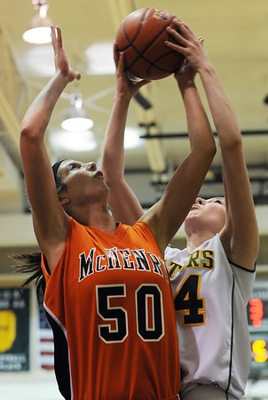 Sarah Nader - snader@shawmedia.com McHenry's Megan Wiesemann (left) and Crystal Lake South's Sara Mickow jump for the rebound during the fourth quarter of Wednesday's game in Crystal Lake on February 1, 2012. McHenry won, 50-41.