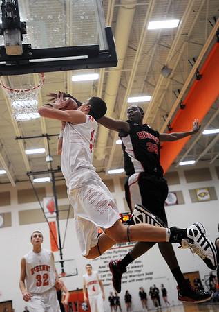 Sarah Nader - snader@shawmedia.com Huntley's Amanze Egekeze (right) jumps to block a shot by McHenry's Robert Tonyan during the fourth quarter of Friday's game  in McHenry on February 3, 2012. Huntley won, 34-29.