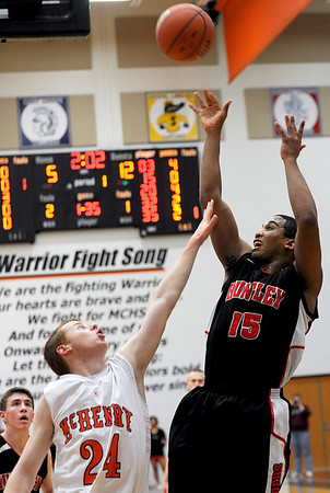 Sarah Nader - snader@shawmedia.com McHenry's Jeff Nicholls (left) jumps to block a shot by Huntley's Bryce Only during the first quarter of Friday's game in McHenry on February 3, 2012. Huntley won, 34-29.