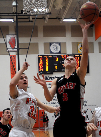 Sarah Nader - snader@shawmedia.com Huntley's Jake Brock (right) is guarded by McHenry's Jamie Rammel while he takes a shot the first quarter of Friday's game in McHenry on February 3, 2012. Huntley won, 34-29.