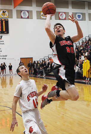 Sarah Nader - snader@shawmedia.com McHenry's Danny Glick (left) watches while Huntley's Troy Miller takes a shot during the first quarter of Friday's game in McHenry on February 3, 2012. Huntley won, 34-29.