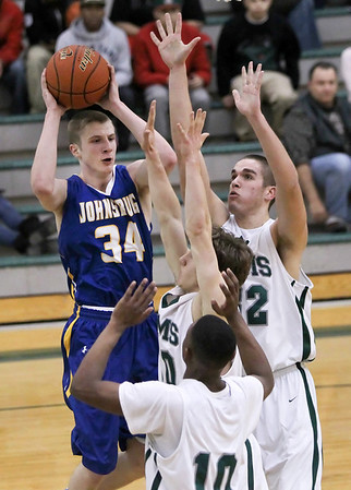 Candace H. Johnson - Shaw Suburban Media Johnsburg's T.J. Sigmund (34) looks to pass the ball against Grayslake Central's Savonte McWilliams (10), Danny Reed and Casey Boyle (32) in the third quarter during the FVC Fox Division matchup game at Grayslake Central.