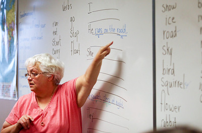 Lauren M. Anderson - landerson@shawmedia.com Mary Lou Glenn of Woodstock points out the word road on the white board as a noun during an English as a Second Language class at McHenry County College on Friday. Glenn volunteers her time as a tutor for the ESL class. (02/03/2012)